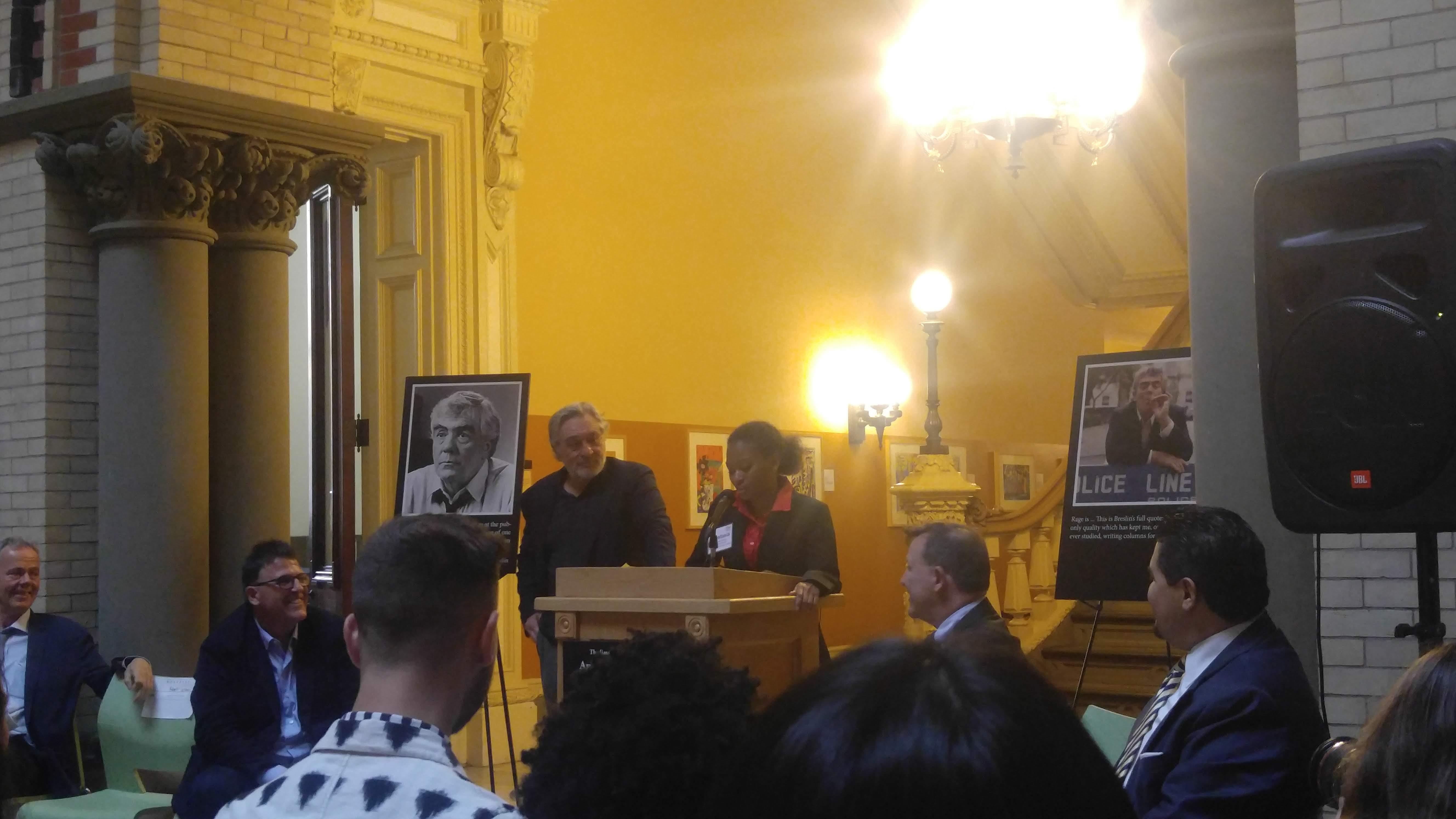 senior prestasia aldridge speaking at a podium at the does tweed headquarters with robert de niro