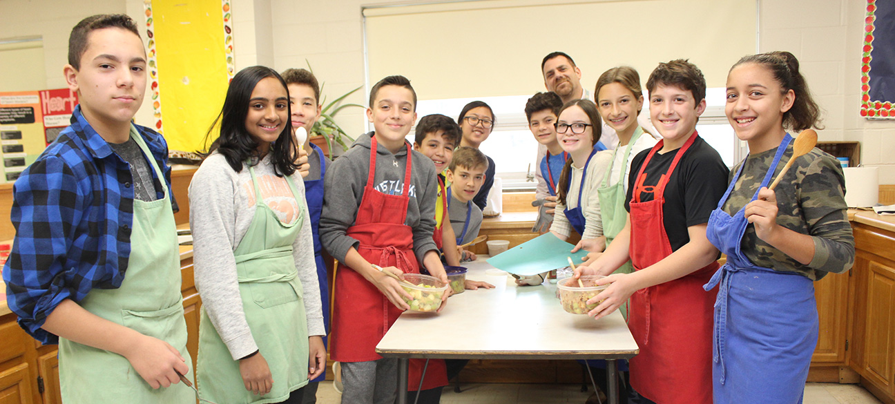 Seventh graders bake apple pie with Mr. Yaeger.