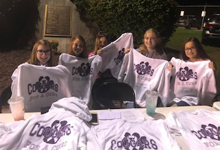 """Students selling """"Cougars for a Cure"""" t-shirts at the football game."""
